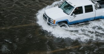 White truck driving through flooded street