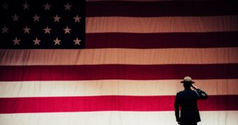 silhouette of military member saluting a large American flag