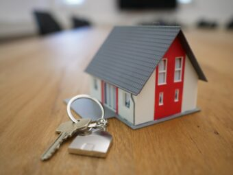 tiny house figurine with a set of keys on a table