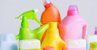 Colorful cleaning bottles and sprays lined up next to one another.