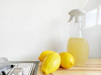 Lemon cleaning spray bottle on kitchen counter next to lemon.