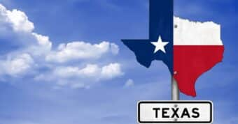 The state of texas on a sign with the texas flag surrounded by clouded skies.