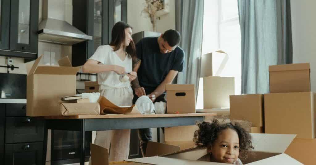 A mom and dad preparing for a move in their kitchen while their daughter is playing in a cardboard moving box.