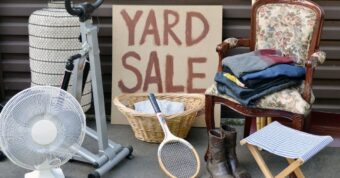 A Yard Sale sign surrounded by a small white fan, tennis racket, floral arm chair, folded up pile of clothing, and a lamp