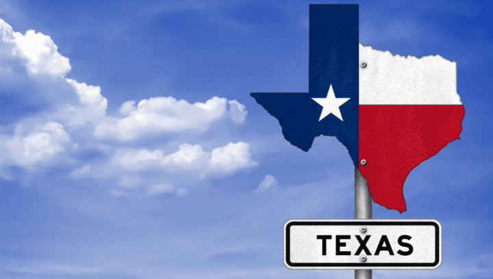 sign showing state of Texas against blue sky